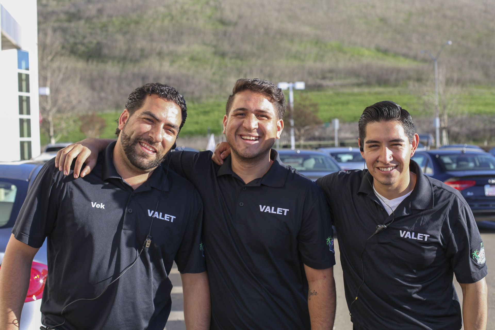 Three valets smiling