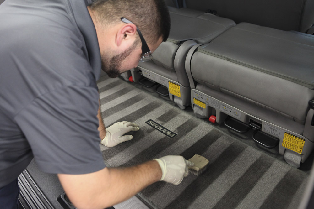 Our worker brushing a trunk carpet